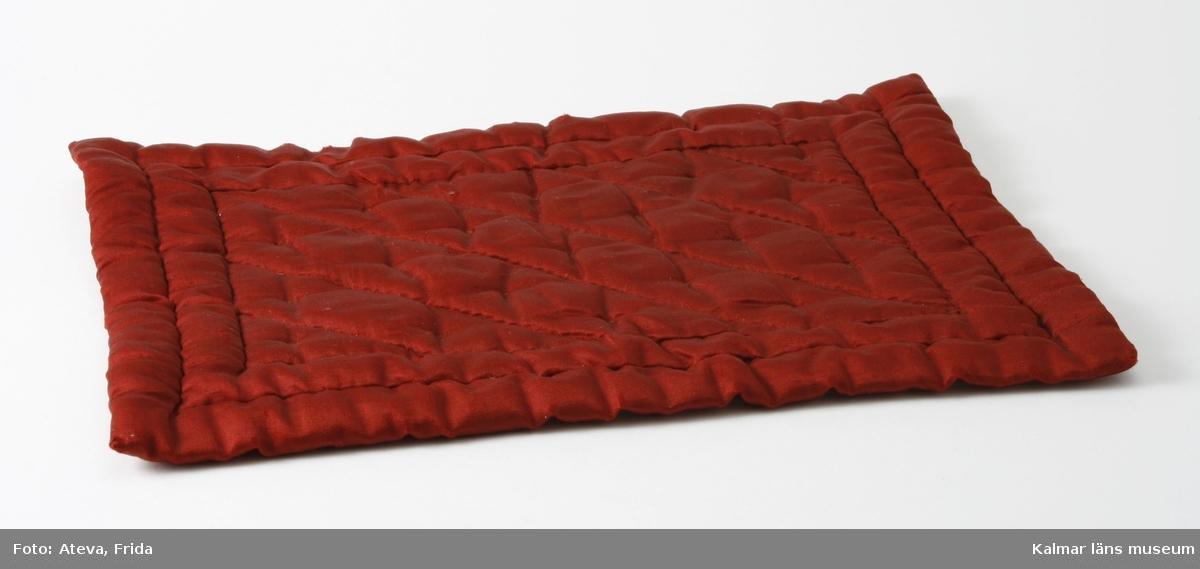 KLM 28568:35:4. Täcke till docksäng. Av mörkröd matlaserad siden. Fodrad med vit tuskaftad bomullsväv. Något slitet i kanterna. KLM 28568:35:1-4 hör samman.