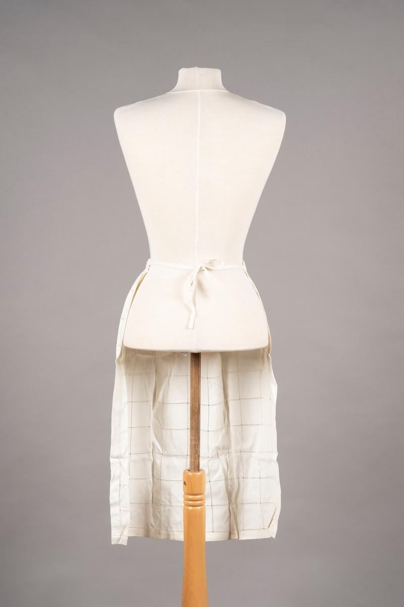 Et forkle med dekor av hullsøm. Forkleedet er av bomull. Det er bånd på hver side av midjekanten for å knyte den rundt livet.
