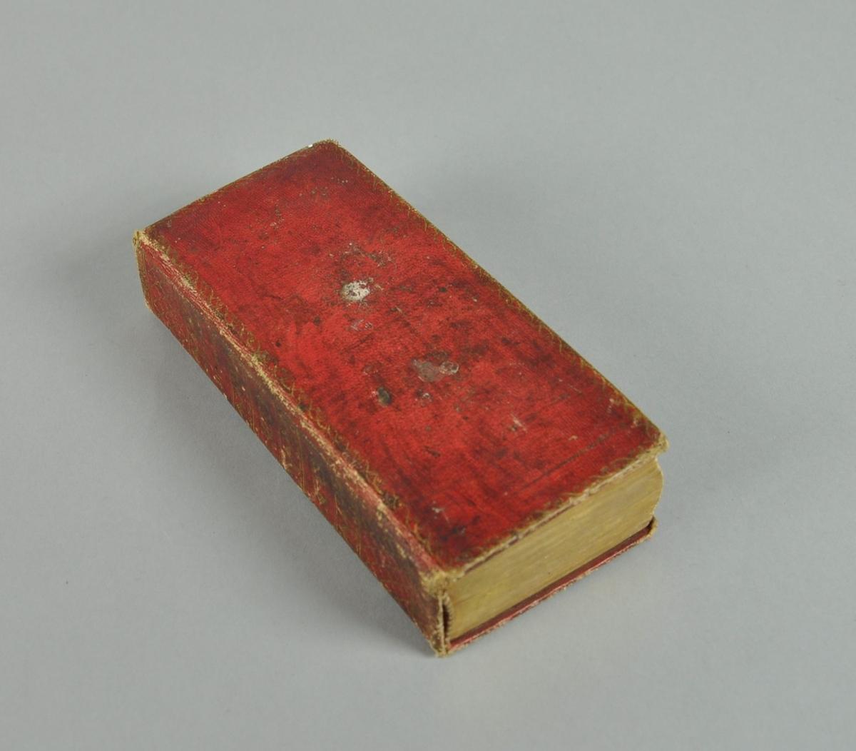 Boken har rødt skinnbind og mørkegrønt papir på innsiden med påtrykte blomster.