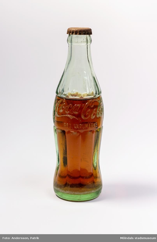 """Coca-Cola i glasflaska från i mitten/slutet av 1950-talet. Flaskan är tillverkad i grönaktigt glas. Loggan """"Coca-Cola REG. VARUMÄRKE"""" är inristat i glaset. Glasflaskans form är inspirerad av kakaobönan. Det geniala med flaskan är dess greppvänliga form med dess särpräglade utseende som gör att man känner igen den även om den greppas i totalt mörker. Glaset splittrades heller inte om flaskan tappades i marken. I början tillverkades flaskorna i färgerna blått, grönt och glasklart glas.  Glasingenjören Alexander Samuelson som formgav flaskan har koppling till Sverige. Han föddes nämligen i Kungälv den 4 januari 1862. Under sina ungdomsår arbetade han på Surte glasbruk. Vid 21 års ålder flyttade han med sin storebror till USA, där han fortsatte att arbeta på olika glasbruk och blev så småingom chef. I början av 1910-talet anordnades en tävling för att designa en flaska till Coca-Colan. Tävlingen vann Alexander och hans glasbruk. 1915 tog Alexander Samuelson patent på denna  geniala utformning av Coca-Colaflaskan, en av världens mest välkända varuförpackningar.  Eftersom livsmedelslagen i Sverige hade förbud mot koffein och fosforsyra, kunde inte Coca-Colan börja säljas i Sverige förrän 1953 då förbudet upphäves. Det var då Pripps bryggerier som tog hem lincensen för att börja tillverkningen av den amerikanska drycken i Göteborg, Malmö och Sundbyberg.  Coca-Colan hade först svårt att konkurrera med storheterna som sockerdricka, Champis, Festis och Zingo. Det var först i slutet av 1970-talet som försäljningen ökade ordentligt."""