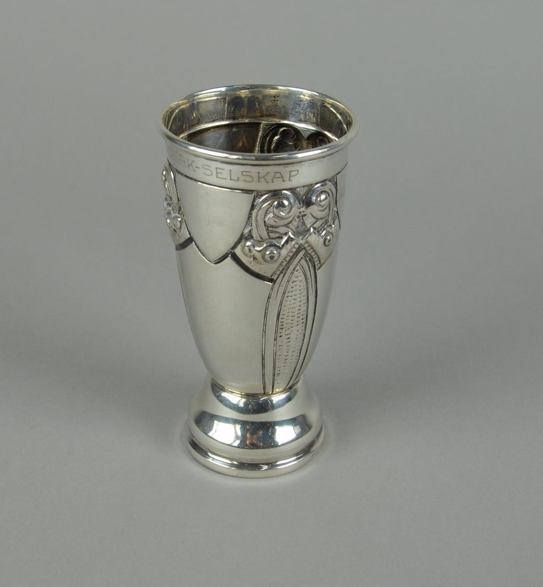 Pokal av sølv. Pokalen har sylindrisk form med innsnevret bunn. Utgående sokkel med profilert form. På korpus er det gravert dekor i dragestil.