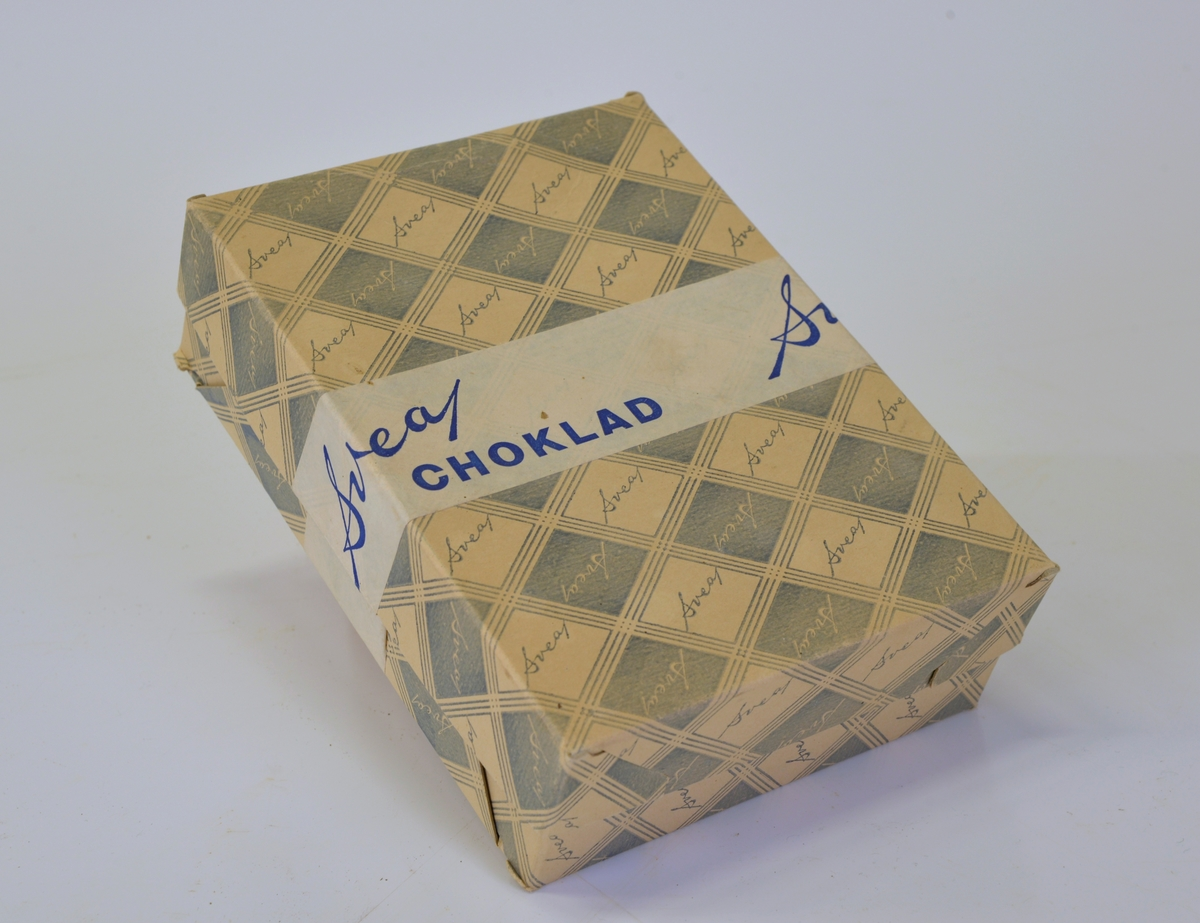 """Rektangulär ask med rutigt mönster i vitt och blått. I varje ruta texten """"Svea"""". Vit klisterremsa tvärs över asken med texten """"Svea choklad"""" i blått. Från Arne Ekströms handelsmuseum."""