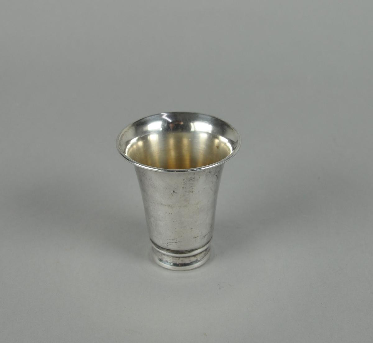 Pokal av sølvplett. Er innfelt nederst, og randen er utstående.