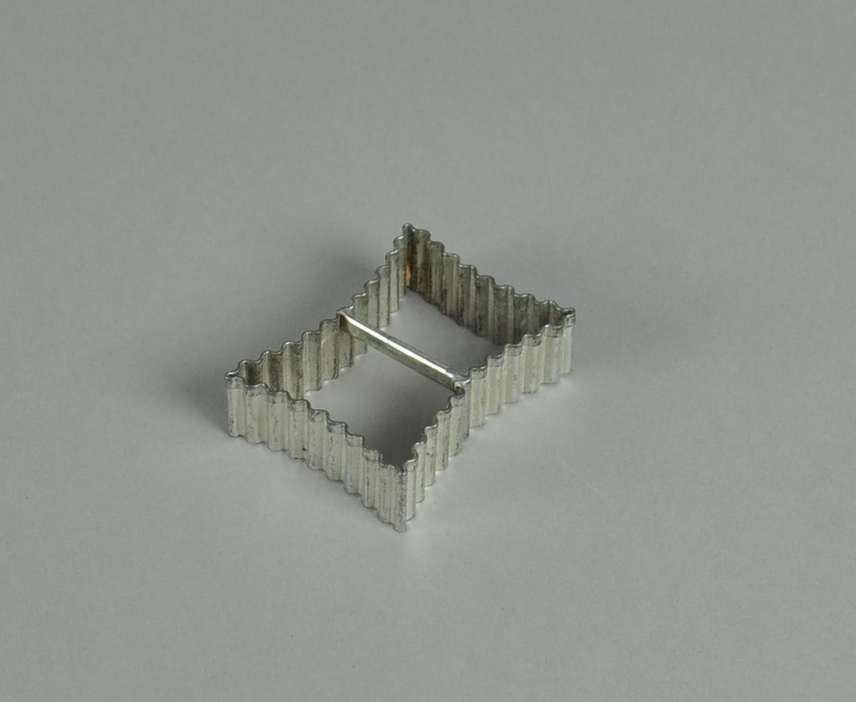 Kakeform av aluminium. Rund form med bølgete profil og hank på midten.