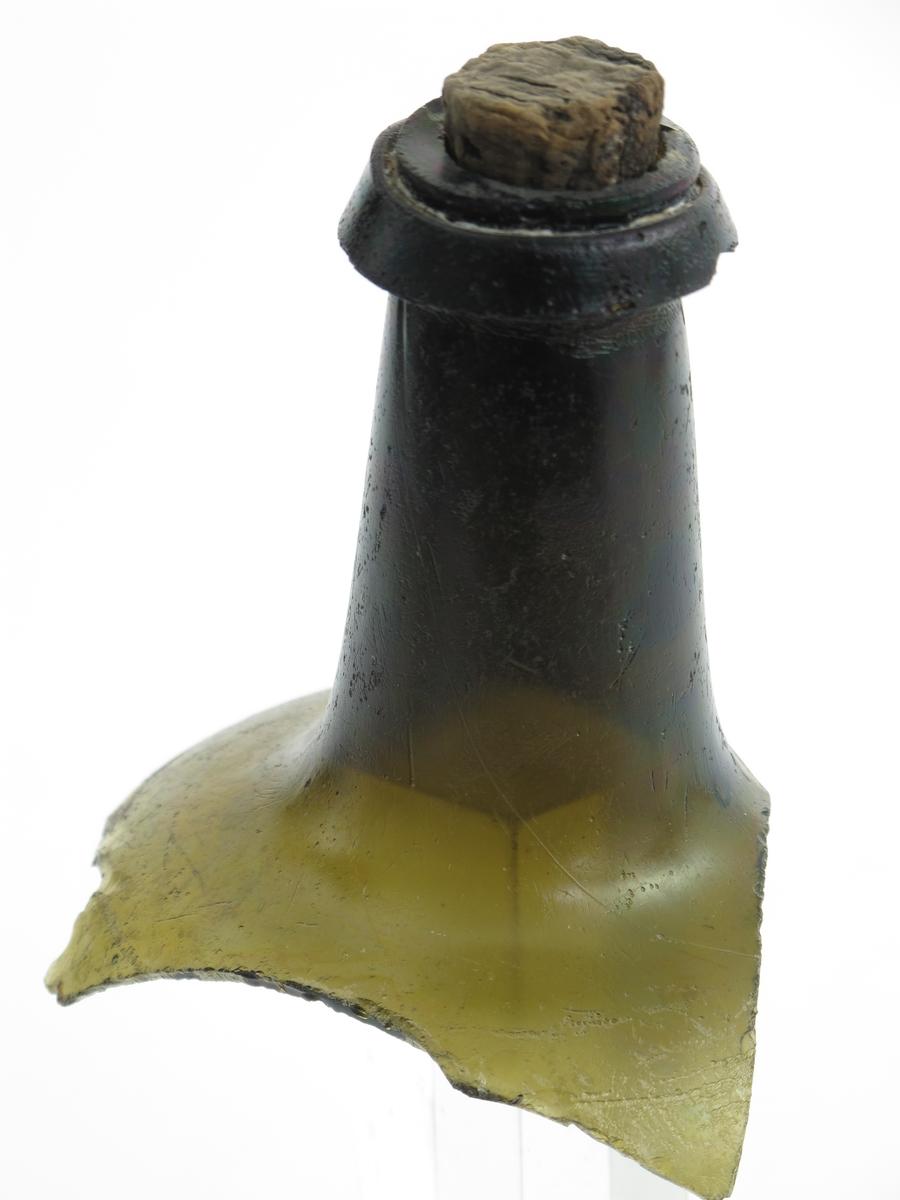 Flaskehals av  butelje, med kork.  Grønt   glass.    Litt av rund skulder, bred  forholdsvis kort hals, litt skrå.  Kraftig skrå munningsbrem, smal kork H 3,2.