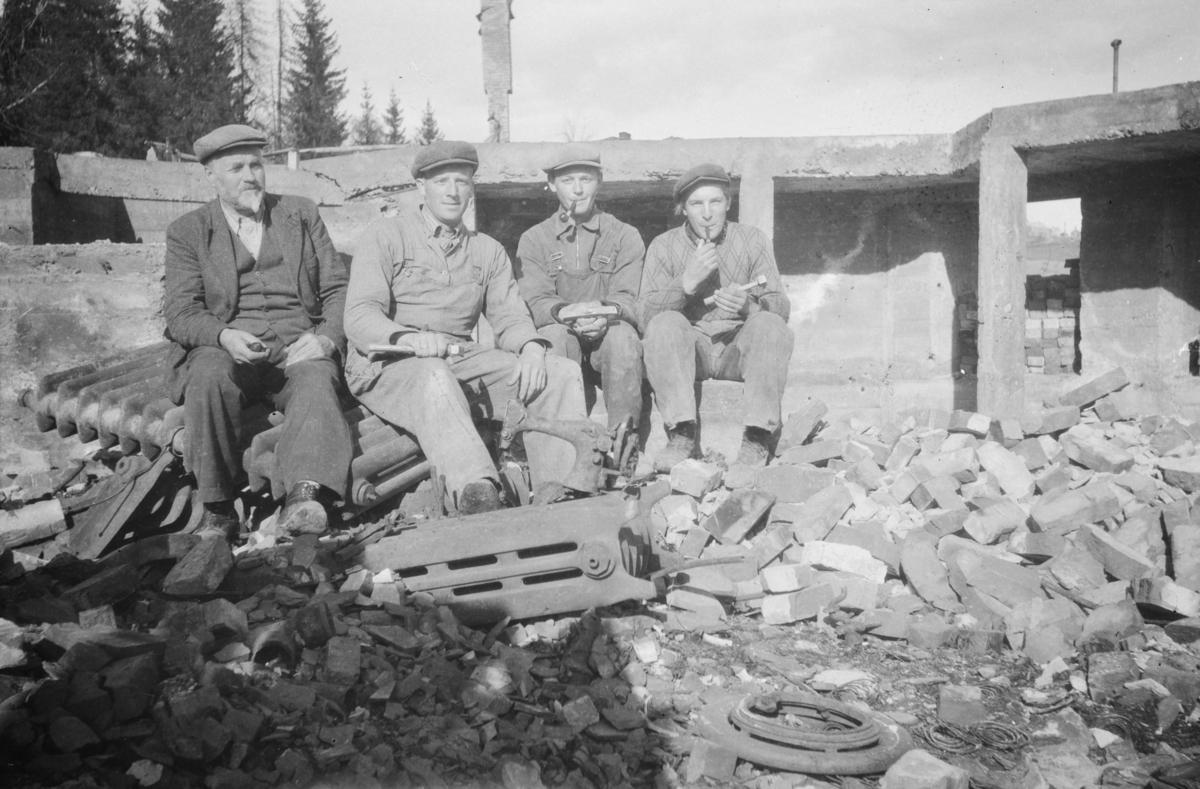 Fire menn sitter ved grunnmuren og rester etter Austlid Hotell som brant under krigshandlingene i 1940. Fra venstre Anders Austlid, Olav Børresen, Gunner Solbjørg og Sigmund Melgårdsbakken