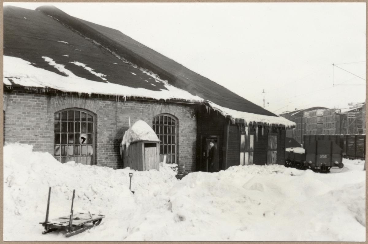Lokstall vintertid med elektrifierat spår i bakgrunden.