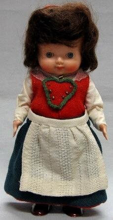 Flickdocka i hudfärgad plast med målade strumpor och skor. Brunt hår. Röd bindmössa,röd väst med hjärtlapp, blå yllekjol med röd kjolskoning, vit skjorta, vitt förkläde, vit tyllsjal.