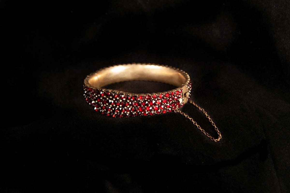 Ett armband, tätt besatt med slipade röda granater. Infattade i förgylld metall, troligen silver. Armbandet något avsmalnande åt sidorna.Smycket ligger i specialgjord svart, ask med röd sammet invändigt och ett snäpplås.  Inga stämplar på armbandet.