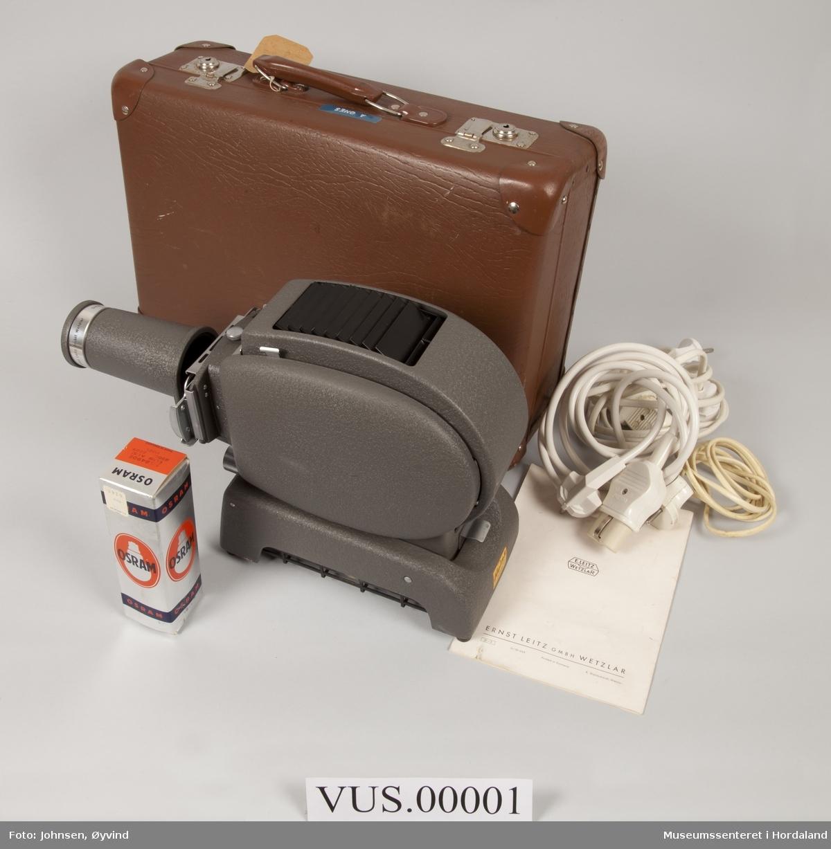 Liten brun koffert med lysbileteframvisar Leitz Prado 250. Med bruksanvisning, reservepære Osram i originaløskje, straumledning og to skøyteledninger. Kofferten har ei ramme av finer, lokket er dekt med mønstra papir. Kunstskinn eller papp på utsida.  Adresselapp i papp heng på handtak: A. Ones Hundvin pr Bergen. Blå Dymolapp i plast på lokket merka A ONES.