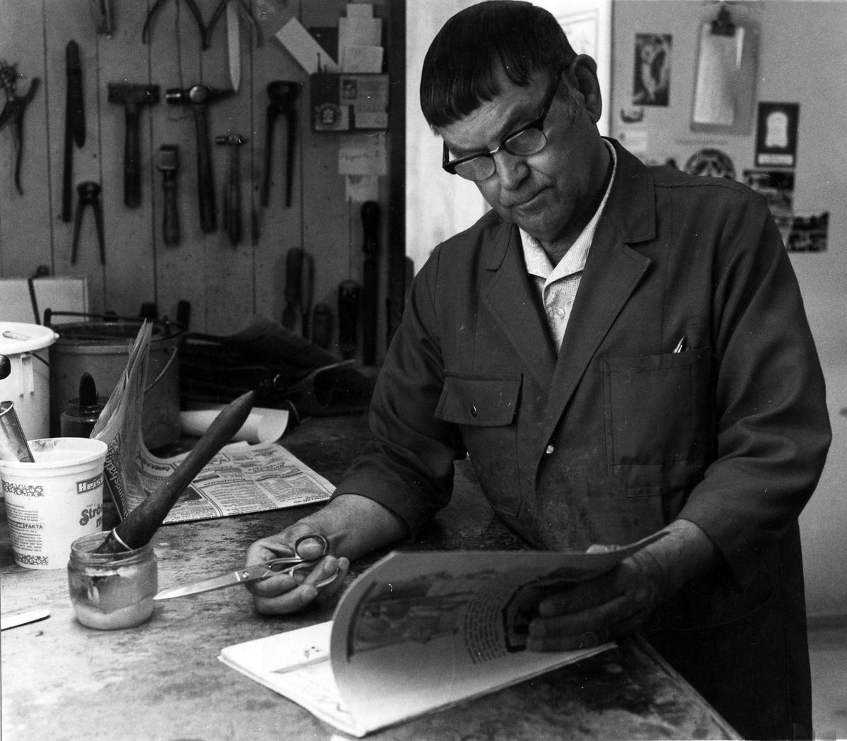 En man i glasögon och arbetsrock, står i en verkstad och blädrar genom ett pappershäfte. I högra handen håller han en sax. Åke Georgson (f 1910) började som bokbindare i kvarteret Gustaf 1 år 1932. Flyttade då fastigheten revs 1967 till en lokal vid Torggatan 7. Verksamheten nedlades i september 1982.