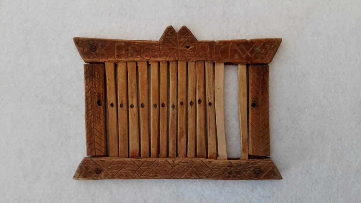 Form: Firkanta. 1vævgrind.  Liten firkantet vævgrind for baandvæv 13,5 x 10,1 cm. Forsirt med strekornamenter og bokstaver. (Sjå orginalkatalog.)  Gave fra Ingebrigt Andersen Rislag, Vik.