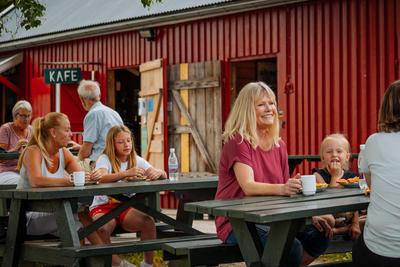 Foto av personer som sitter ved bord på brygga.