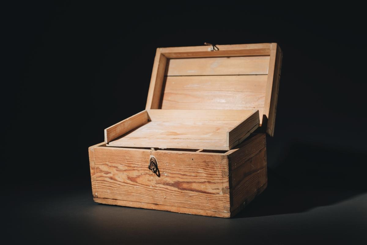 """Skrin med lock i omålat trä. Locket har ett handtag och en hasp av metall. Handtaget beläget mitt på lockets ovansida. Inristat i locket text: """"H.M. NAJADEN. 1928 H.M. JARRAMAS (53) 4:8 417"""". Därjämte inristade teckningar av en fyr och tbå korslagda ankare."""