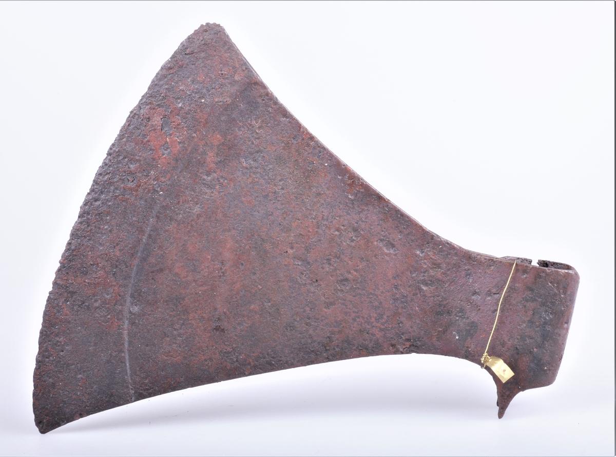 Øks av jern fra vikingtiden, skjeggøks. Ganske tynt økseblad som blir noe tykkere de ytterste 3-4 cm mot eggen. To små fliker som som skal peke nedover mot skaftet.
