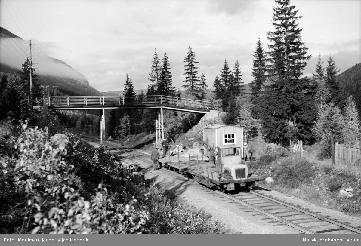 Arbeid med heving av overgangsbro ved Svenkerud km 196,11 i forbindelse med elektrifiseringen av Bergensbanen. Arbeidstrallen litra Robel 10 ble benyttet til transport av materialer.