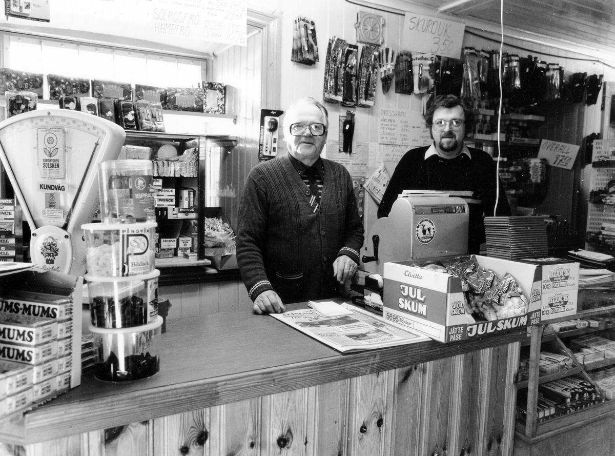 Bild innifrån Gunnar Johansson KB i kvarter Repslagaren 2 där specerier, jordbruks- och trädgårdsprodukter säljs. Två män vid kassan, en är ägaren Gunnar Johansson.
