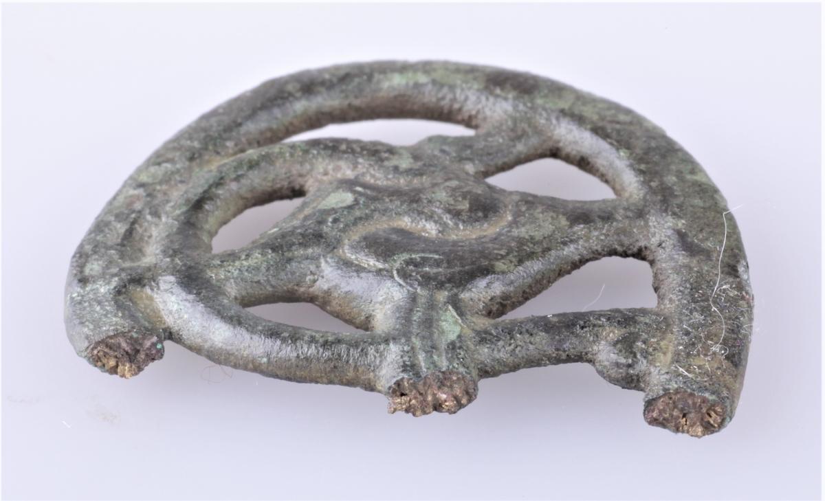 Nøkkelskaft støpt i bronse med gripedyrsmotiv. To deler; a) hoveddelen har avlang buet form, b) del falt av hoveddelen.