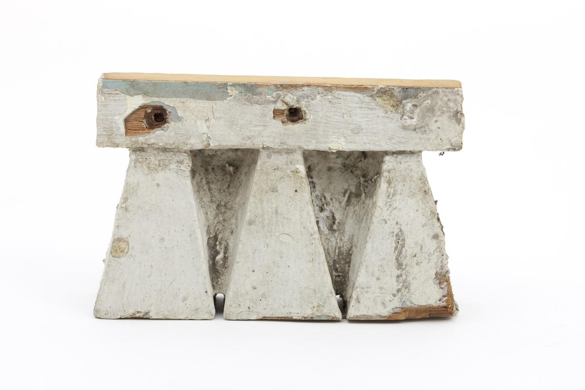 Utskåret og malt bord i treverk. Opprinnelig har den hatt en lys blå farge, overmalt med lys grått. 2 spikerhull.