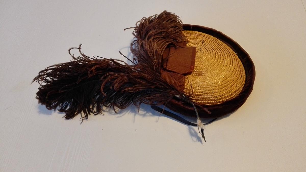 Fletta og sydd saman av naturfarga strå. Bremmen bretta opp ca. 3 cm og kanta med fløyel (brunt). Hatten som er kalott- liknande, er pynta med lange, farga (brune) strutsefjør, ca. 18 cm, og 3 cm brei rips-sløyfe. Svart strikk under haka til å halda hatten på plass.