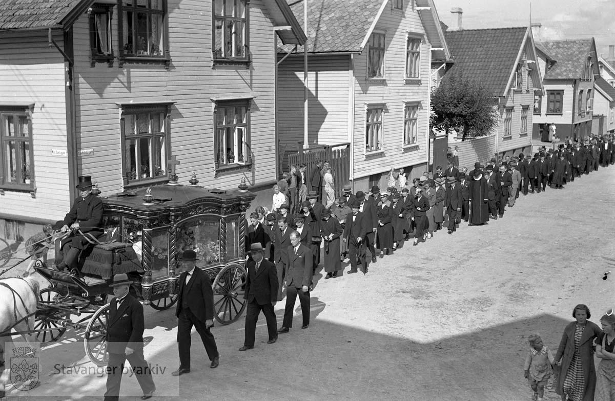 Begravelsesfølge med hest og kjerre. Gravfølget går langs Løvdahls gate. Niels Juels gate inn til venstre i front. På vei mot Eiganes Gravlund.