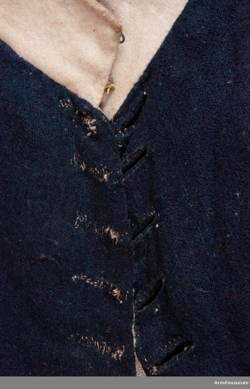 """Fracken är vänd någon gång, vilket innebär att sömmarna sprättats och tygstyckena vända ut och in för att sys ihop igen. Detta gjordes för att förlänga brukningstiden på plagget. Därför har fracken igensydda knapphål på ena sidan av öppningen. Märkt på insidan """"LS No 2""""."""
