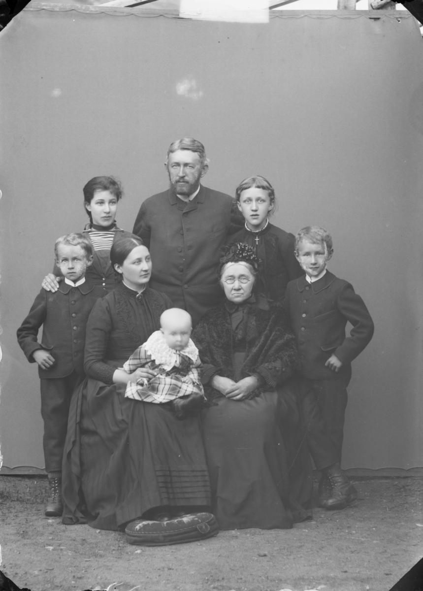 Familiebilde med antatt 3 generasjoner med bestemor, foreldre og 2 eller 3 døtre og 2 sønner.
