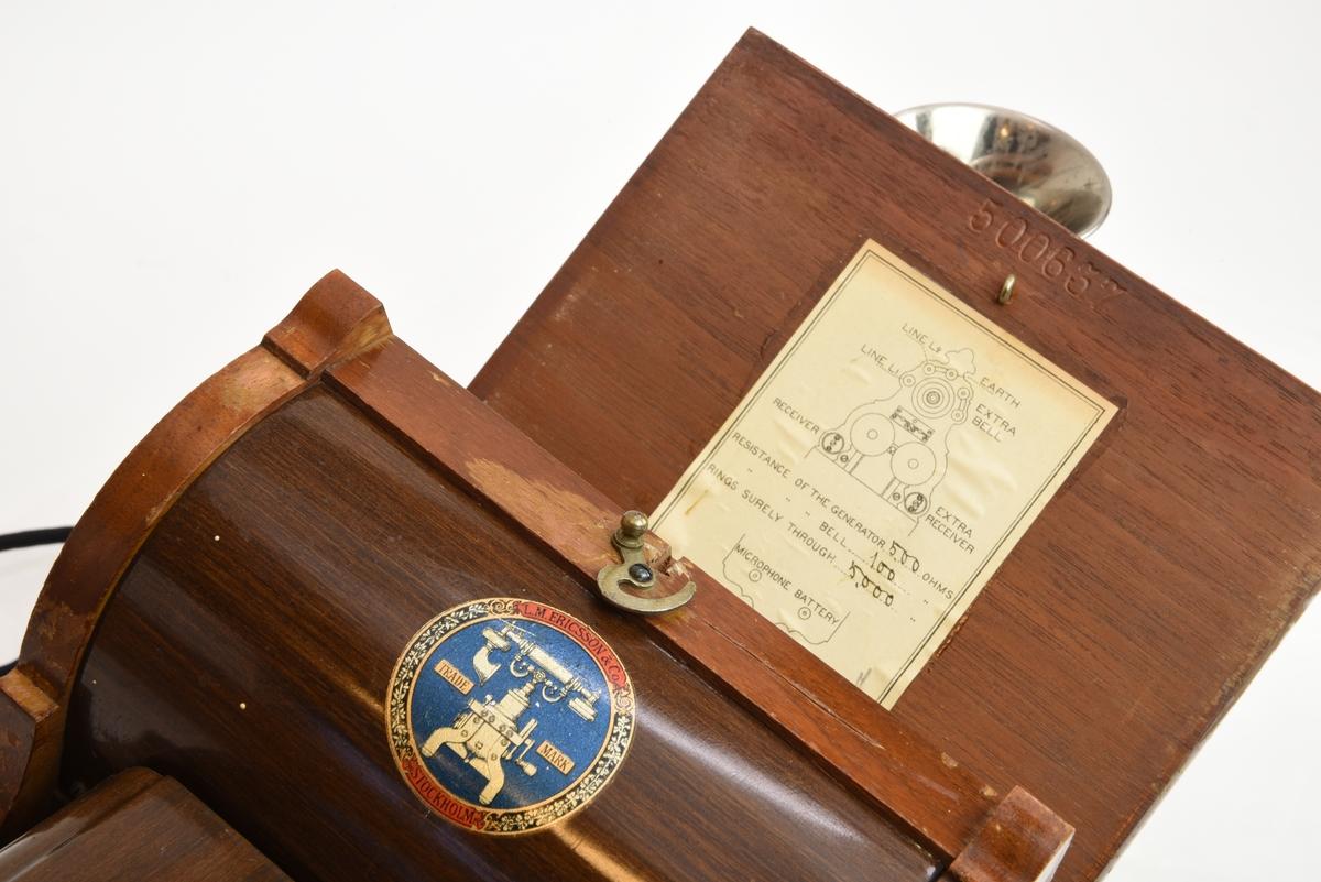 En väggtelefon av trä från tidigt 1900-tal gjord av L.M. Ericsson.  Mikrofonen är monterad direkt på telefonen och ser ut som en metalltratt, hörapparaten är handhållen och är kopplad till telefonen via en elkabel. På väggtelefonens överdel finns skruvbara mässingsfästen. Nedanför mikrofonen finns en ringklocka och ett svart påskruvat metallhölje med påmålad ornamentik. Mitt på väggtelefonen sitter en utstickande trälåda som innehåller mekaniska komponenter som rör på sig när man rör på den vev som sticker ut ur lådans högra sida. På undersidan av locket till trälådan finns en pappersetikett med en förteckning över telefonen. Nedanför trälådan finns ett hyllplan som täcks av en metallkåpa (med målad träimitation), i det utrymmet ska det finns ett batteri.