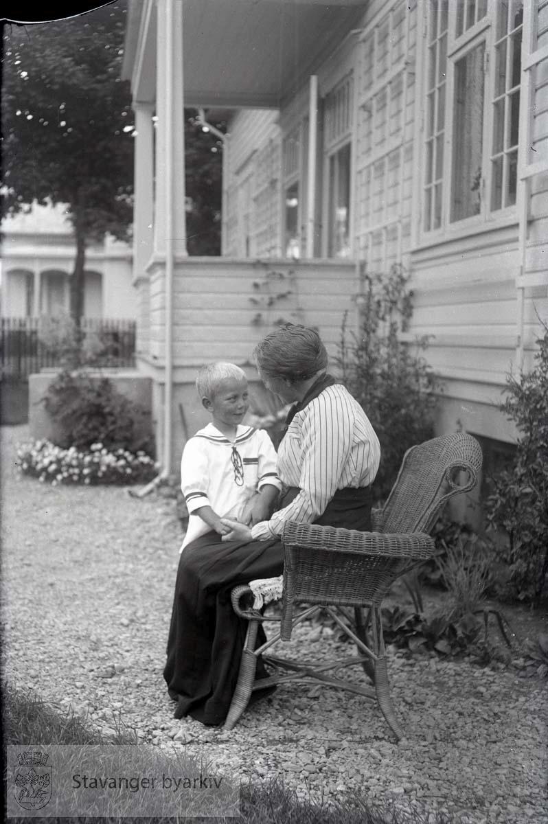 Dame og barn sittende utenfor huset i Jelsagaten