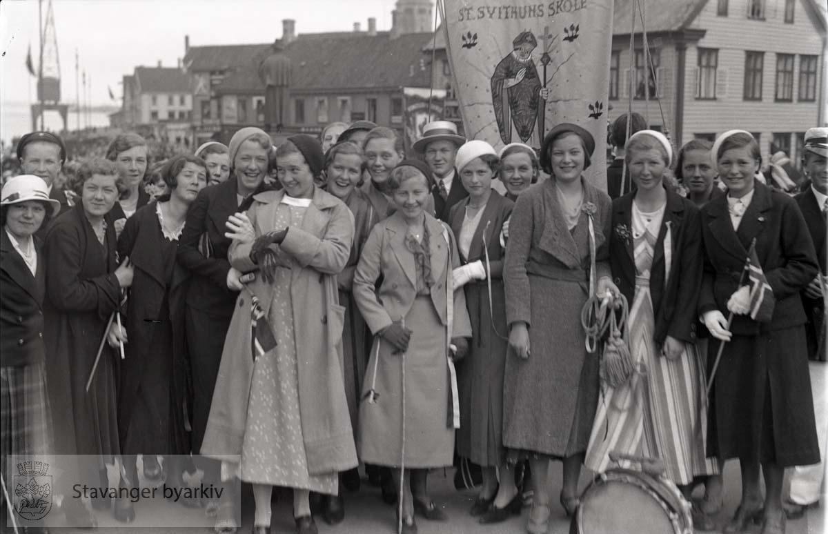 Jenter og gutter fra St. Svithun skole pyntet til nasjonaldagen. Skolefane i bakgrunnen.