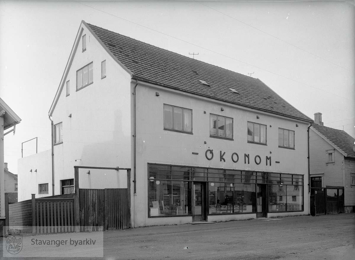 Opprinnelig bolighus i tre, innkjøpt av Forbruksforeningen Økonom i 1916. Bildet viser bygningen etter sterk ombygging. Vinduer er skiftet og veggene murpusset.