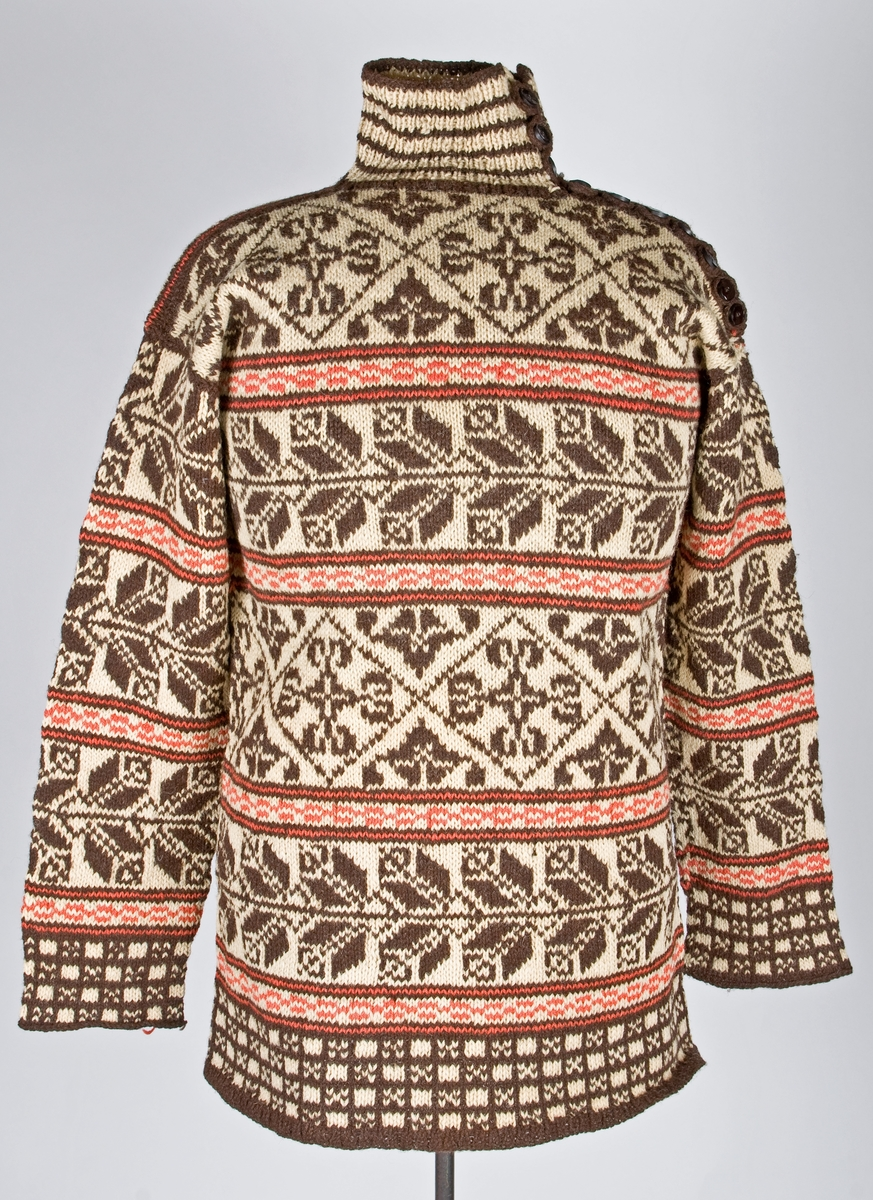 Stickad tröja men hög krage. Knäppning på vänster axel och upp längs halskrage. Mönsterstickning i mörkbrunt och rött mot naturfärgad botten.