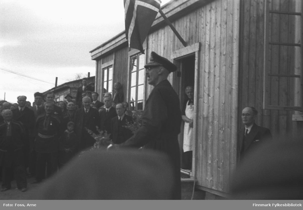 Kongebesøk i Langnes juli 1946. Kong Haakon VII reiste landet rundt for å se på krigsødeleggelsene og gjenreisningsarbeidet. Kongen holder en tale utenfor Tana Turiststasjon. Bland publikum, venstre side fra Kongen fylkesmann Hans Gabrielsen, og høyre side Per Fokstad, ordfører i Tana