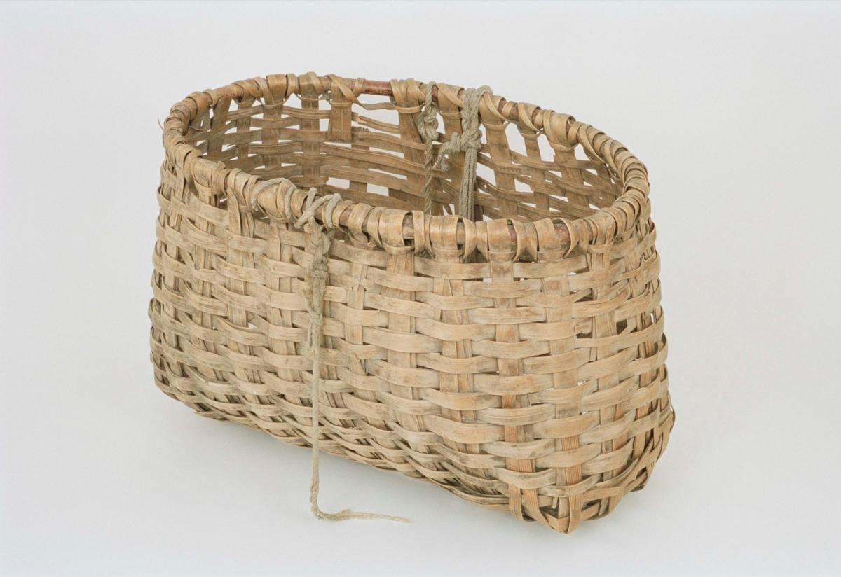 Stor flätad klövjekorg av furuspån, rundad och kupad i botten.