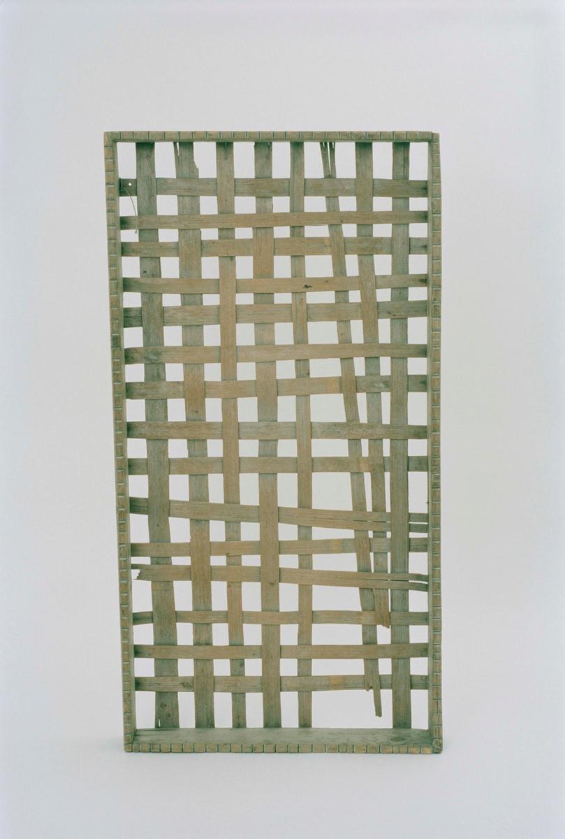 Rektangulär låda med träram av furu, botten av flätad spån fastspikad på ramen. Ramen med ristade skåror.