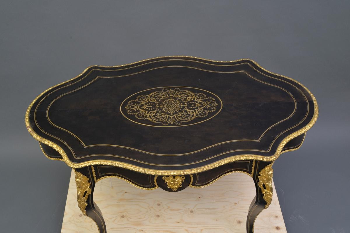 Ovalt bord (fransk), konstruksjon i heltre som er finert. Bordet har messing intarsia og pyntebeslag i metall. Overflate er antakeligvis malt med svart limfarge og lakkert.