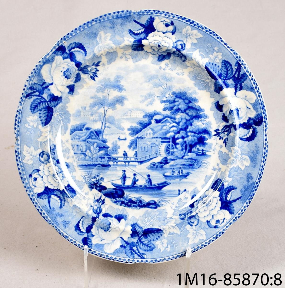 Vit rund tallrik av flintgods med tryckt blå dekor. Dekornamn: 1828 års landskapsmönster. Tillverkare: Rörstrand