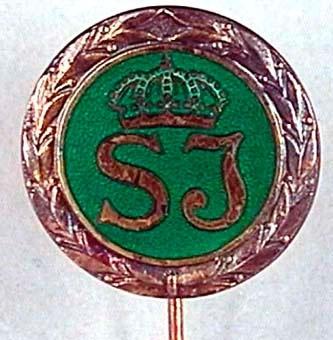 Utmärkelsetecken, runt med nål för fastsättning i kavajslag. Märket är av silver med SJ:s logotyp på grön emaljerad bottenm inom en lagerkrans.