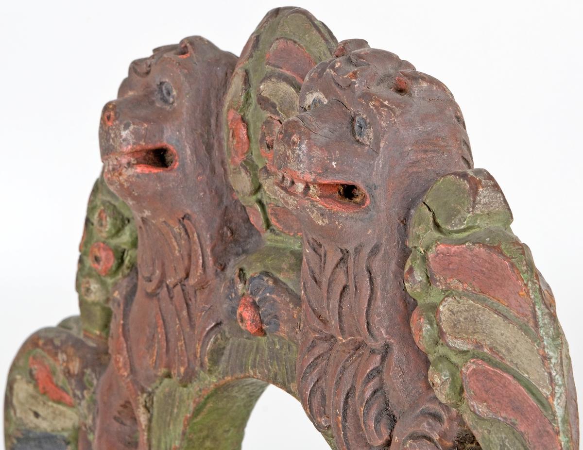 Selkrok av trä, skulpterad och målad i grönt, brunt, rött, svart och vitt. Skulpteringen föreställer två stycken lejon. Rokoko.