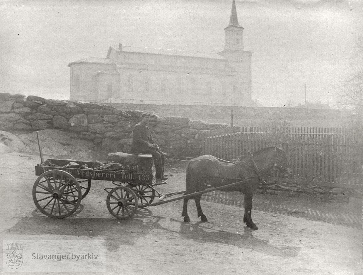 På kjerra står det Vålands Vedskjæreri. Hetland kirke (Vår Frue kirke) i bakgrunnen. Steingard og grind.
