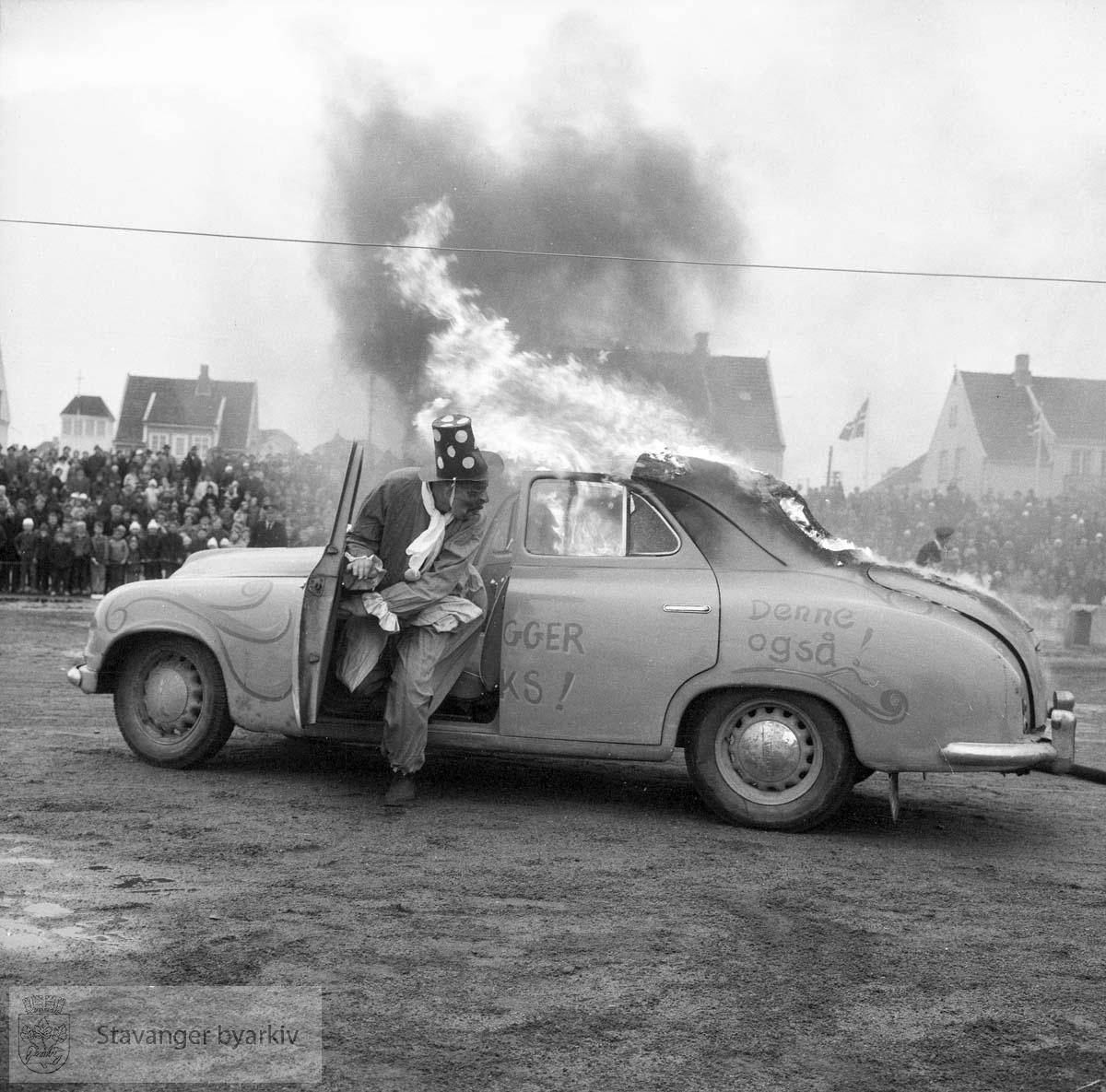 Oppvisning av gammelt og nyere materiell. Karl Jørgensen i klovnedrakt kjører en brennende bil.