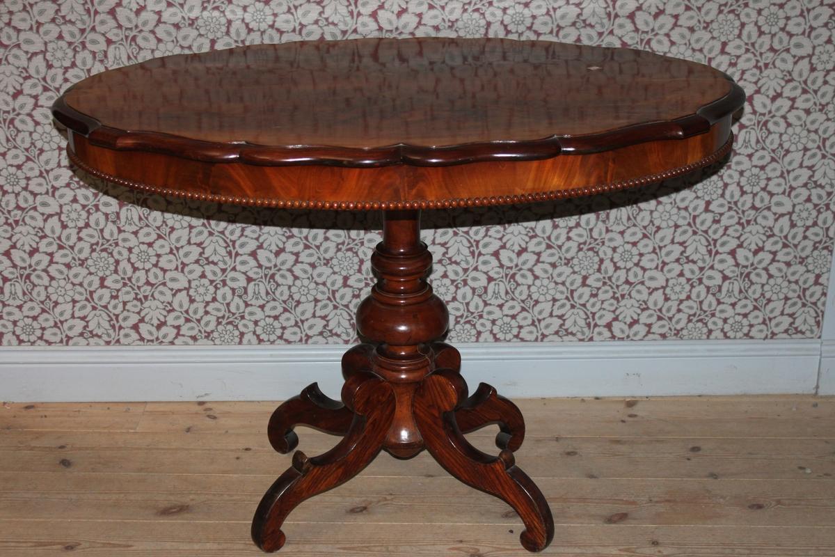 Ovalt pelarbord i nyrokoko. Fanerat i mahogny. Bordsskivans kant går i en böljande form. Sargen är försedd med en pärllist. Pelaren är försedd med fyra svängda ben nedtill.