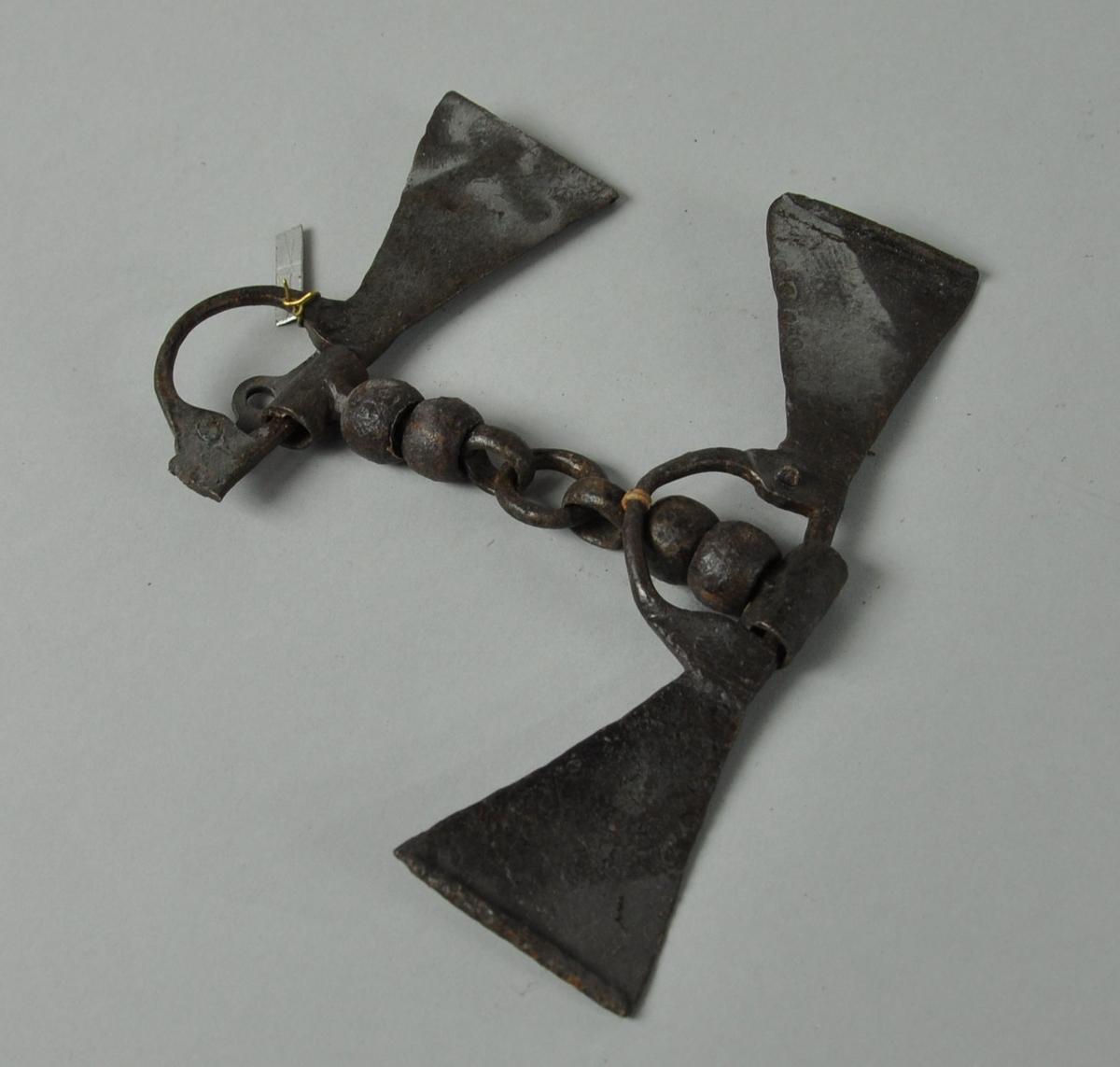 Bissel, leddet med kulestav og ring på midten. To trekantformede plater på sidene, hvorpå den ene trekanten er knekt av.