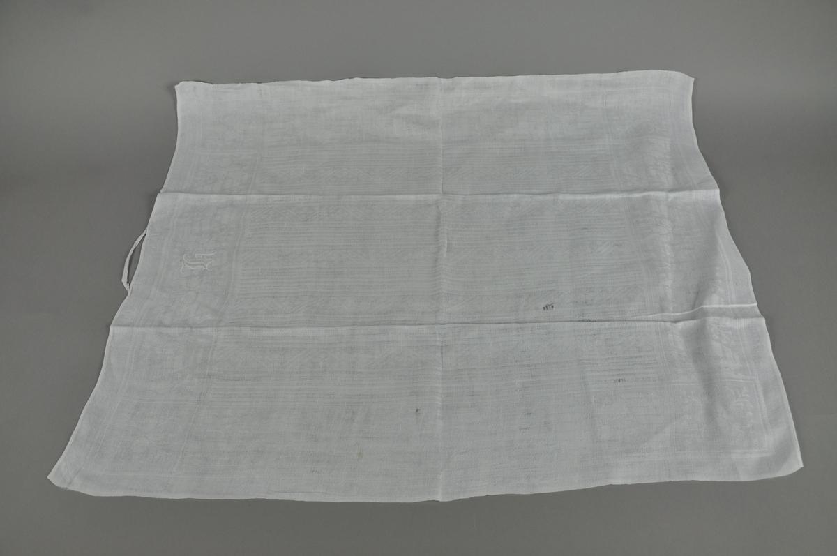 Hvitt håndkle av lin, rektangulær form. Tekstilen er noe slitt.