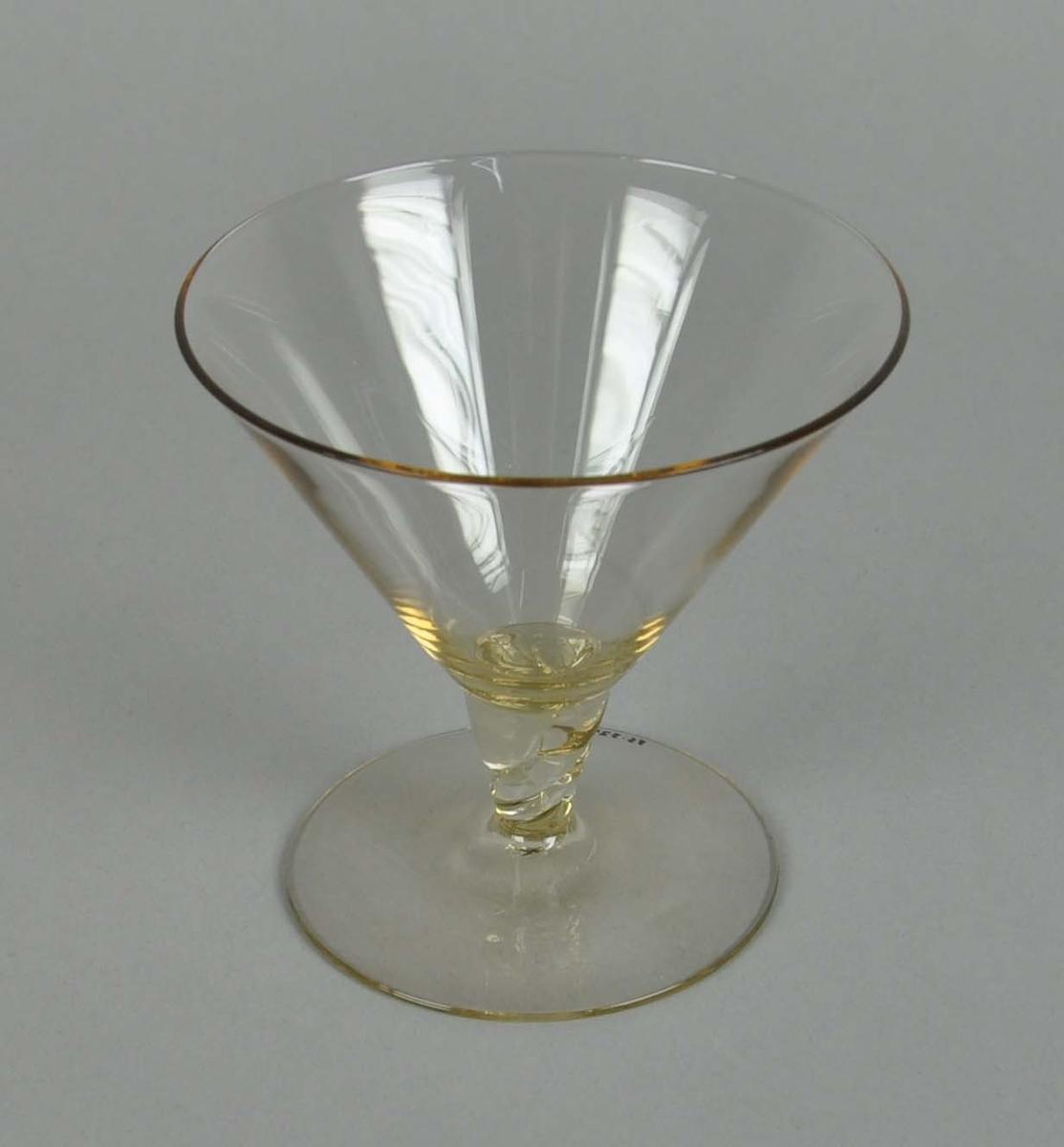 Coctailglass av gult glass. Glasset har y-form med spiralisert stett.