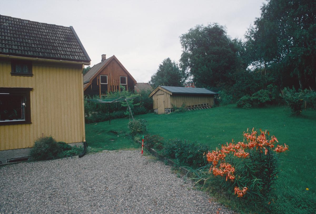 Lillehammer.  Morterudvegen 18A (gult) og 14 (brunt).  Det lille gule uthuset og den brune boligen (Morterudvegen 14) ble revet for å få plass til tunnel for Mesnadalsarmen og etterpå erstattet med nye bygg.  Hage.  Sett mot nord.