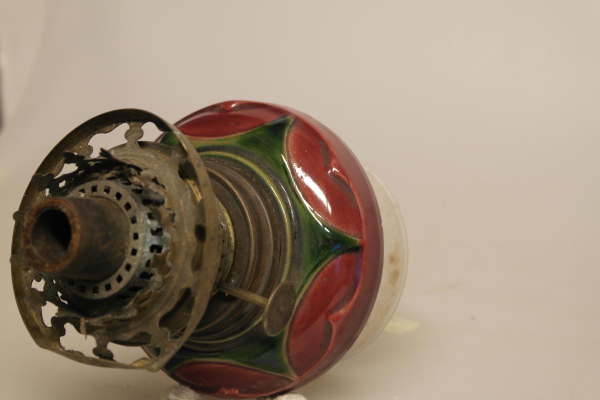 Parafinlampe i glass og malt keramikk, med lampeglassholder i messing. Det er veke igjen i lampen.