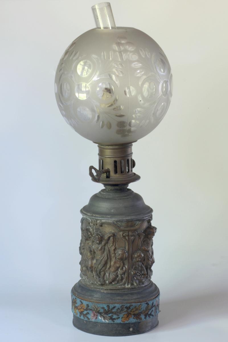 A: Lampe;  B: Kuppel;  C: Perlebroderi : A: bunn sirkelform, hode, lampeglass; B: kule m. åpn. oppe og nede, A: plastisk fig.; B: klart mønster av blomster og  blader; C: bladranke