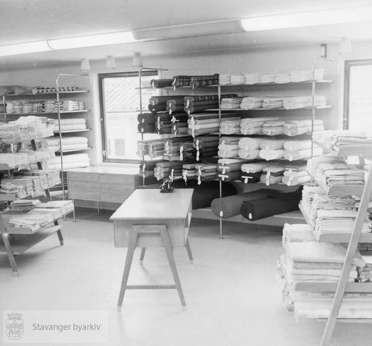 Norem Baade i Kirketaten 22.Utstyrsavdelingen i 2.etg. Hyller med tøyruller, disk og reoler. Utskilt fra PA293.