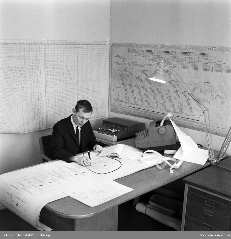 En man på Hallström & Nisses kontor hanterar planering och ritningar med hjälp av en datamaskin.